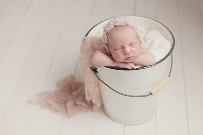 baby in bucket wearing pink bonnet