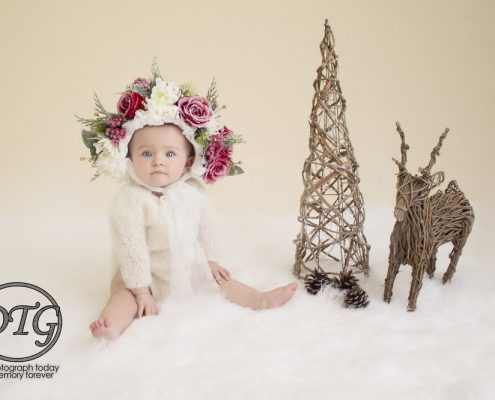 Baby wearing Christmas bonnet during themed shoot